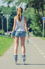 Woman with bottle of water ride rollerblades. Back view.