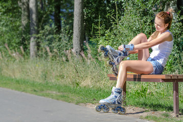 Pretty girl sitting on the bench and putting on inline skates.