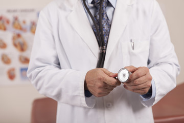 A male doctor holds a stethoscope in his hands.