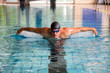Man swims butterfly style in public swimming pool
