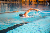Fototapety Man swims front crawl style in swimming pool