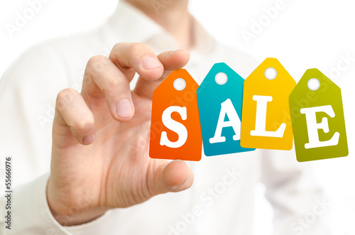 Man holding sale colored labels on white background