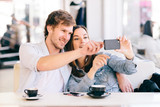 Couple taking photo of themselves with a phone in cafe