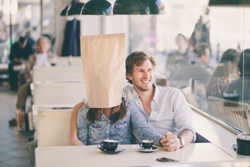Young man sitting in a cafe with his girfriend who's wearing a p