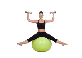 Young beautiful woman sitting on a gymnastic ball with dumbbells