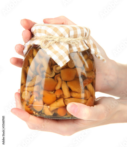 Female hands with delicious marinated mushrooms in glass jars,