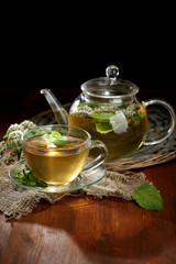Cup and teapot of herbal tea with fresh mint flowers
