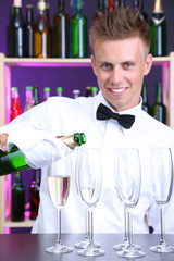 Bartender is pouring  champagne into glasses