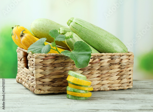 Sliced and whole raw zucchini in wicker crate, outdoors