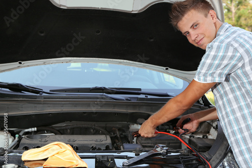 Young driver uses battery jumper cables to charge dead battery