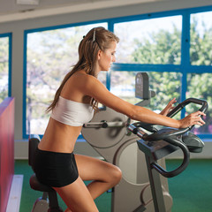 Beautiful skinny woman riding a bike in fitness