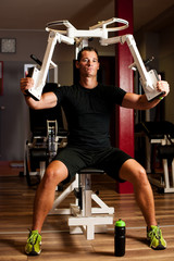 Active sportsman works out in fitness on butterfly machine