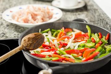 Closeup of cooking vegetables and chicken in a pan