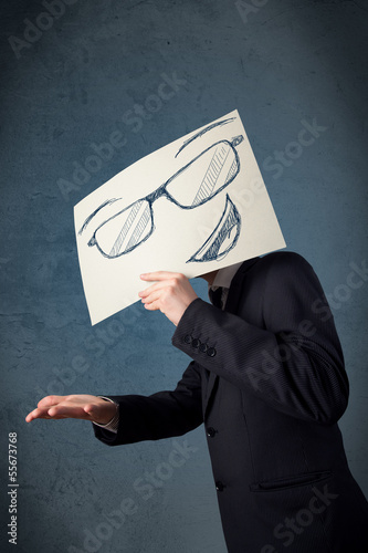 Businessman holding a paper with smiley face in front of his hea