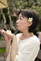 woman enjoying spring frangipani flowers in the garden