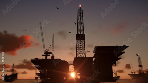 Oil rigs in ocean, time lapse sunrise
