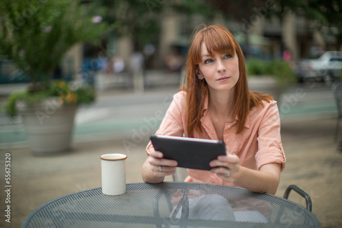 Caucasian woman using ipad tablet computer outdoor