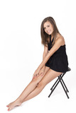 Beautiful young blond woman sitting in black designer chair