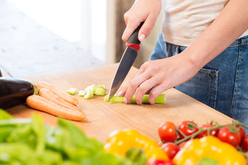 Woman Cutting Celery On Chopping Board