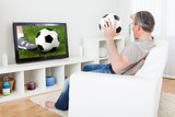 Mature man watching football on television