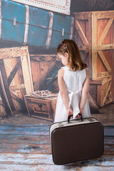 Sad child holding an old suitcase
