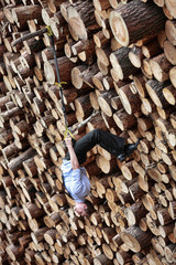 business man suspension workout on the  pile of cut wooden logs