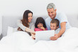 Smiling family lying in bed using their laptop
