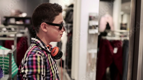 Young teenager trying on sunglasses in fashion shop
