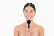 Happy dark haired woman holding powder brush in front of her