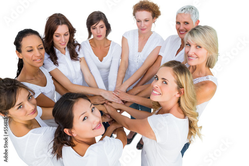 Female models joining hands in a circle and looking at camera