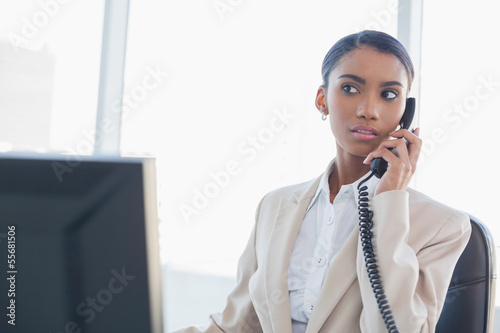 Serious gorgeous businesswoman on the phone