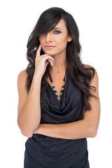 Pensive elegant dark haired model posing with finger on her chee