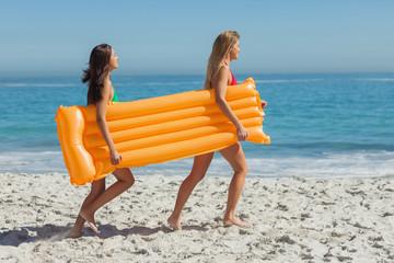 Two pretty friends running holding air mattress