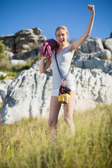 Woman holding climbing equipment and showing muscle