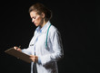 Serious doctor woman writing in clipboard isolated on black