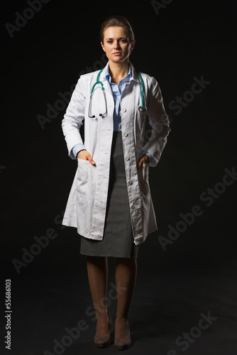 Full length portrait of doctor woman isolated on black