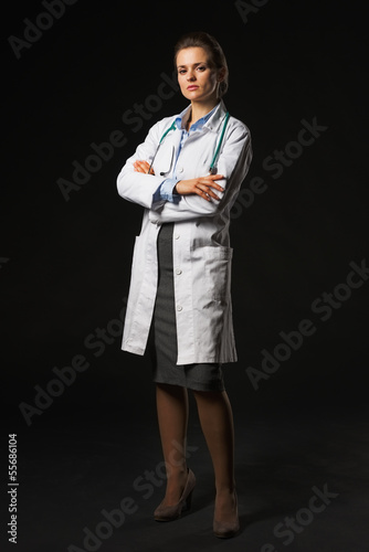 Full length portrait of serious doctor woman on black background