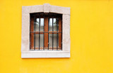 Stone window on Yellow wall background house fasade
