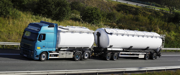fuel truck driving on highway, panoramic.