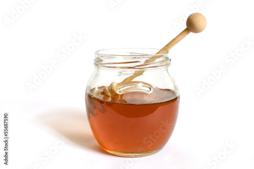 Honey dipper in a jar of honey isolated on white