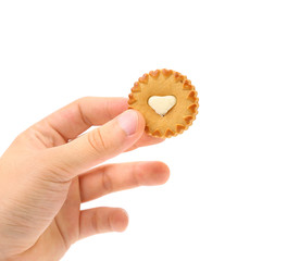 Hand holds biscuits with white heart.
