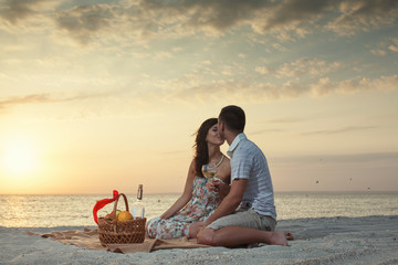 Couple On Beach With Luxury Wine Picnic
