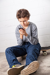 Cool Boy sitting on his skateboard, holding a smartphone