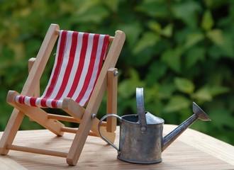 Metallgießkanne und Liegestuhl im Garten