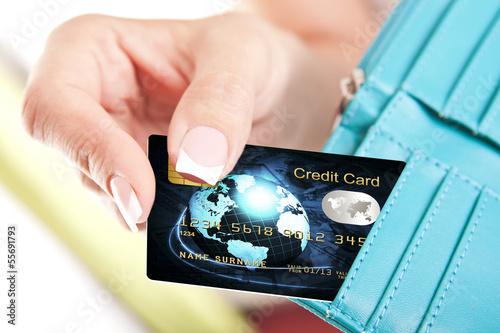 credit card in woman's hand taken out from wallet