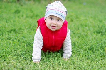 lovely baby in red waistcoat creeps on grass