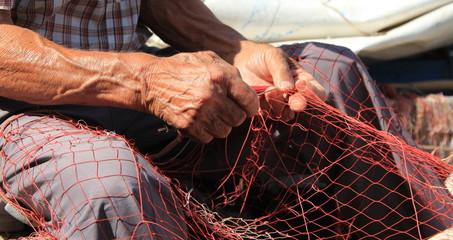 Mani al lavoro su una rete da pesca