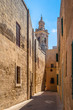 Tiny street in Mdina with limestone buildings and a church