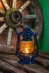 kerosene lamp  against the background wagon wheel
