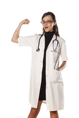 smiling young woman doctor gesture strength with her hand